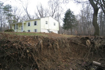 Image of a house at risk from stream bank erosion.