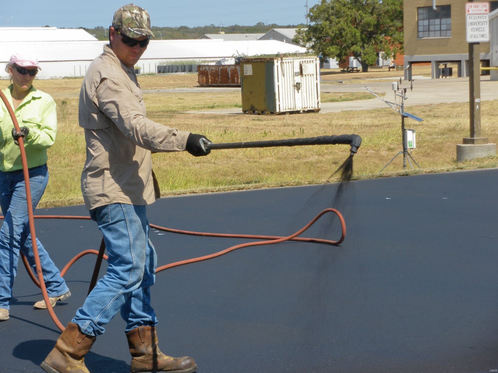 Photo of a paving contractor spraying a coal tar sealant.