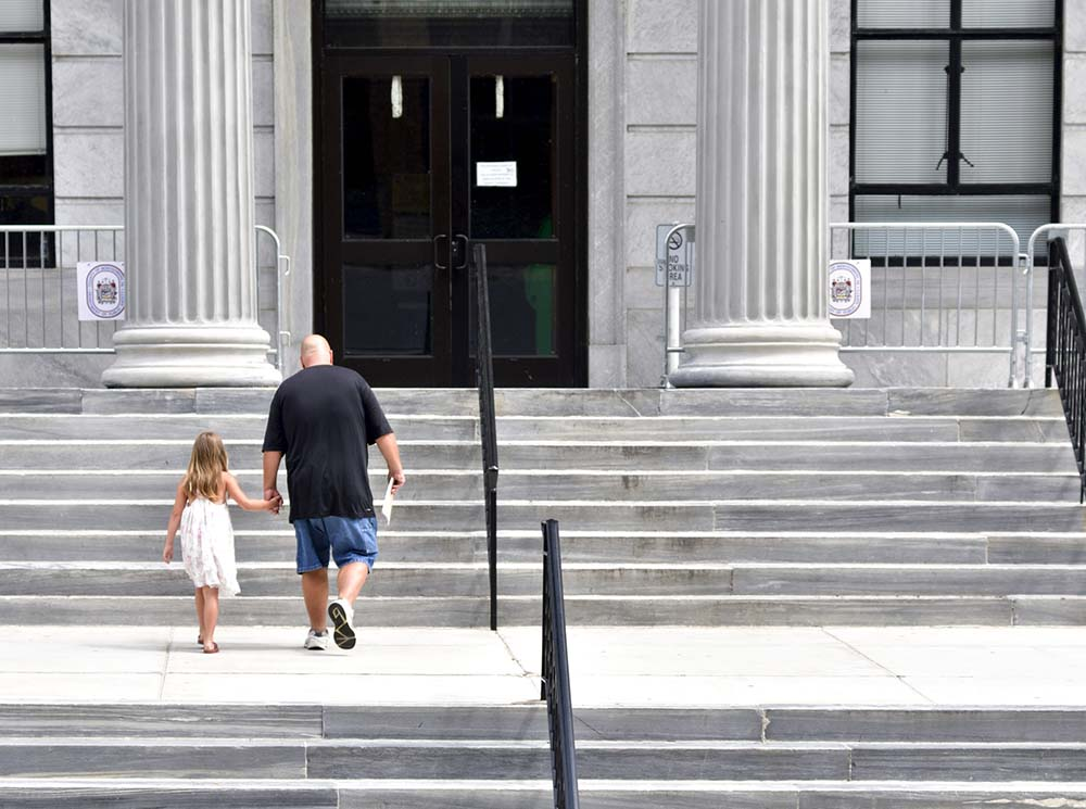 a man and a child walk up court steps