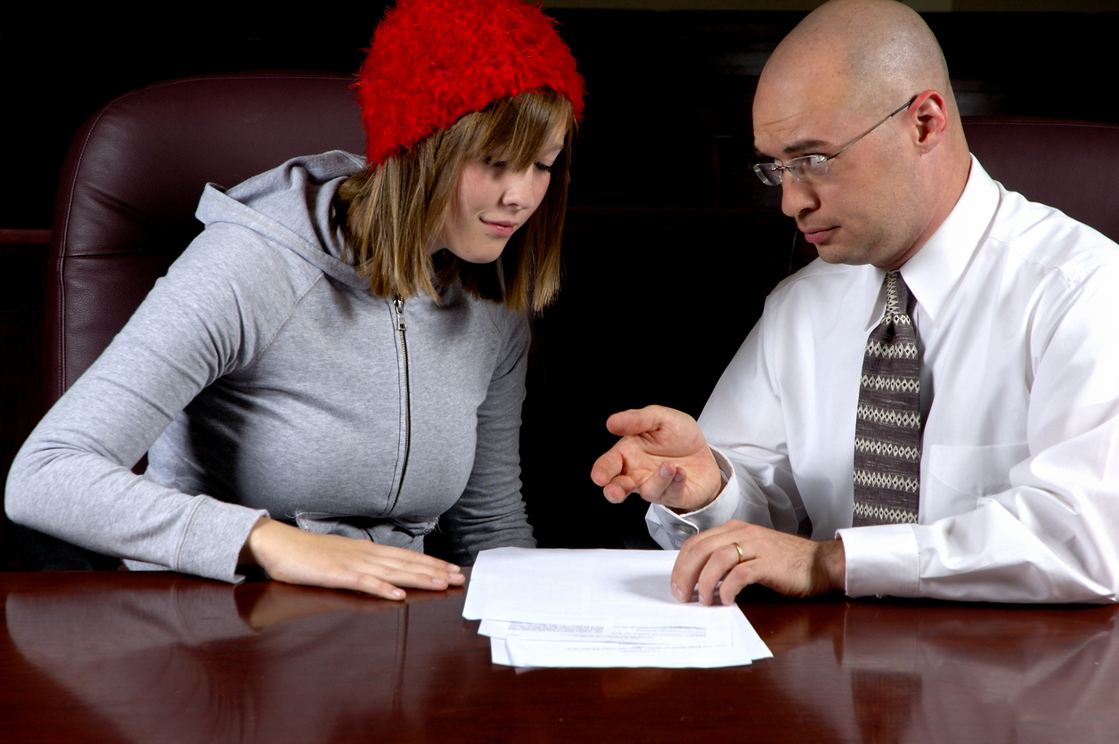 Lawyer helping young adult with paperwork