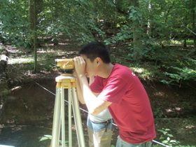 Photo of an intern helping measure a stream channel.