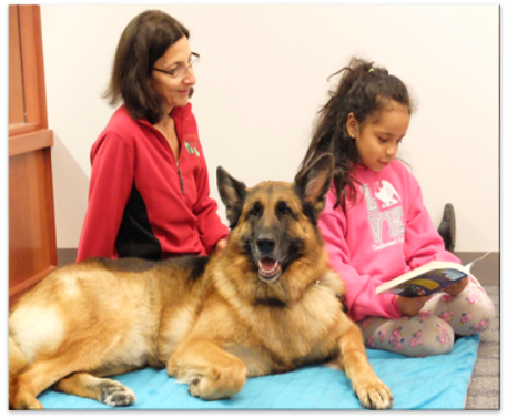 Child reads to a dog at Olney Library