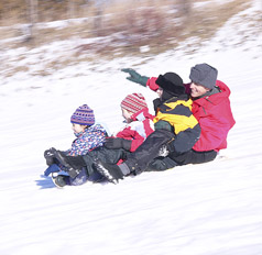 Three kids and one adult  sledding down a hill