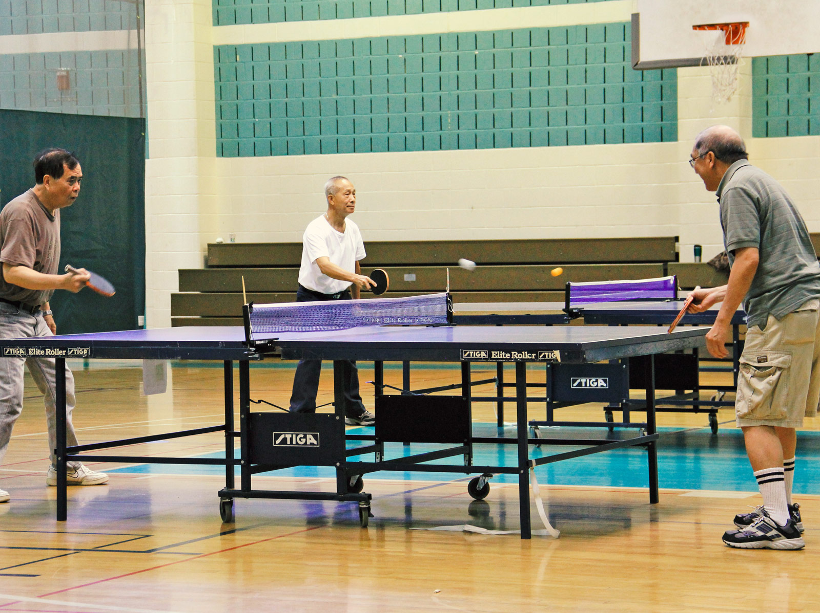 three men playing ping pong